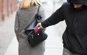 Thief pickpocketing woman's handbag