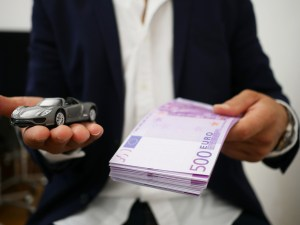 Man holding a car in one hand and cash in another.