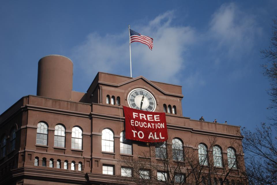 Students hang banner below the historic clock tower of the Cooper Union Foundation building in New York City during a december occupation in protest of the possibility of implementing tuition in the historically free school.