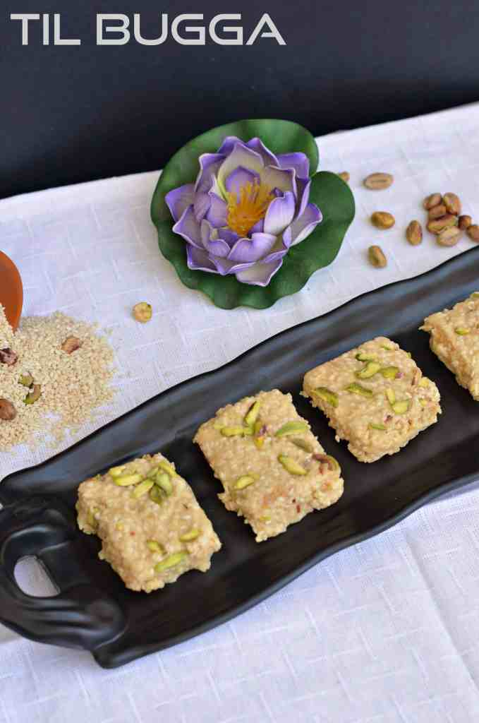 Til Bugga click taken in black serving tray. Flower, pistachio and sesame scattered around the recipe.