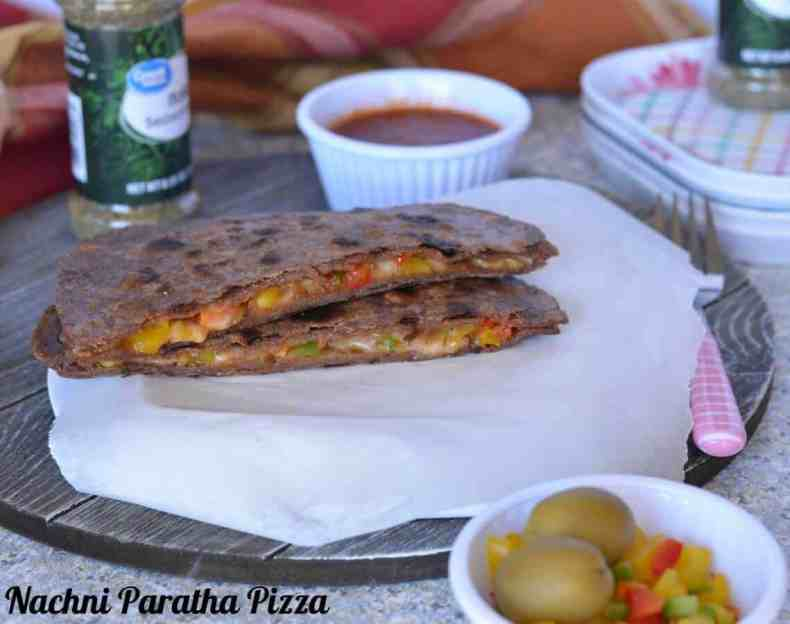 Pizza paratha is a stuffed flatbread which tastes like pizza and popular among kids. It is a fusion between paratha (Indian flatbread) and Italian Pizza. Basically, it is an Indian paratha (flatbread), which is stuffed with pizza sauce and vegetables filling with cheese. Cooked on the stove top like a paratha.