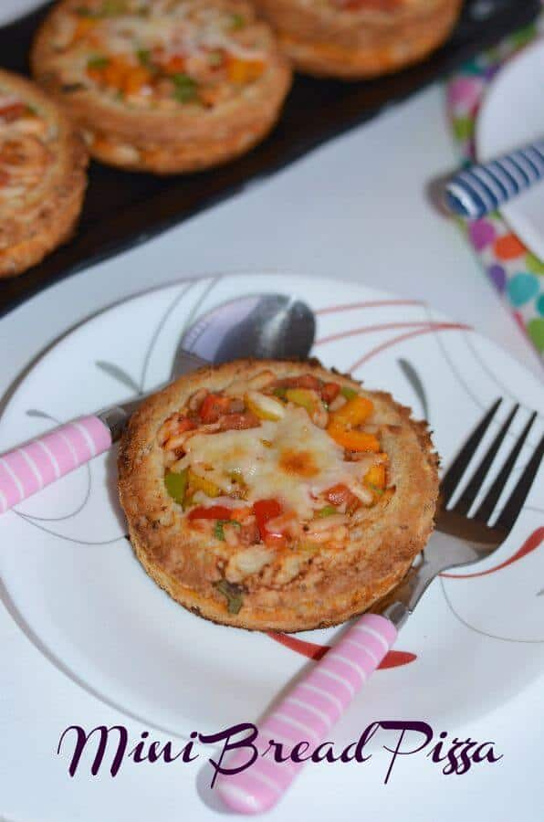 Mini bread disc pizza is a simple, easy and quick bread pizza recipe made with bread slices, filled with crunchy vegetables like bell pepper, olives, onion, tomatoes and finally topped with cheese.  Mini bread disc pizza goes very well for breakfast, lunch or dinner or kids after-school snack.