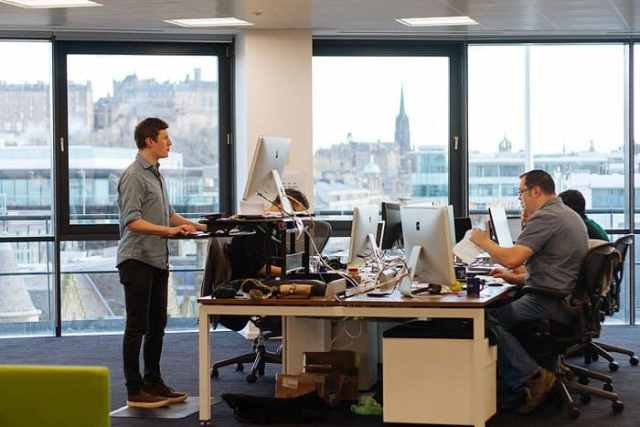 FreeAgent employees at work with a standing desk and two sitting desks