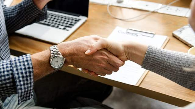 photo of a handshake in an office setting