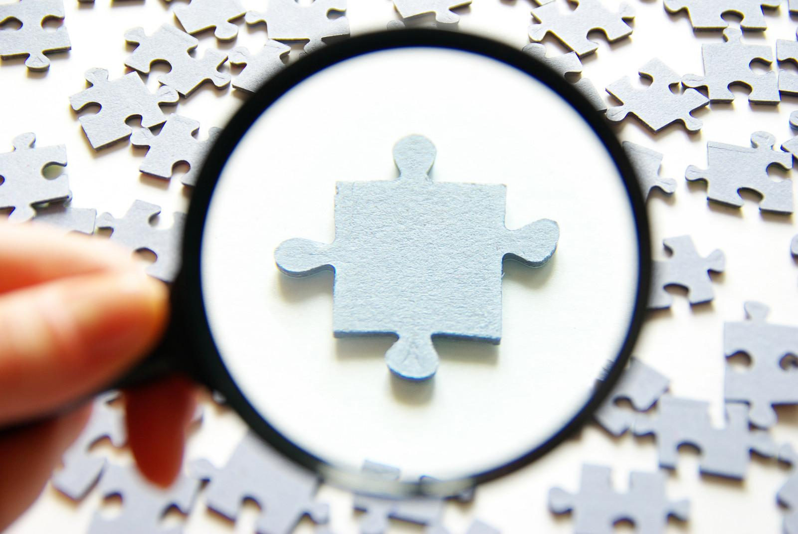 magnifying glass with puzzle pieces