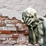 statue covering face in front of old broken brick wall