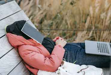 muslim woman in hijab resting with notebook on face