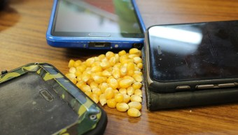 Teléfonos inteligentes al lado de un maiz pozolero