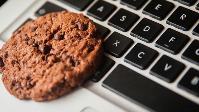 Galleta de chispas de chocolate sobre una laptop