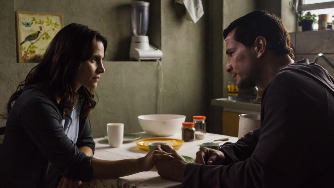 Reseña la morgue maldita hombre y mujer sentados en la mesa tomados de la mano