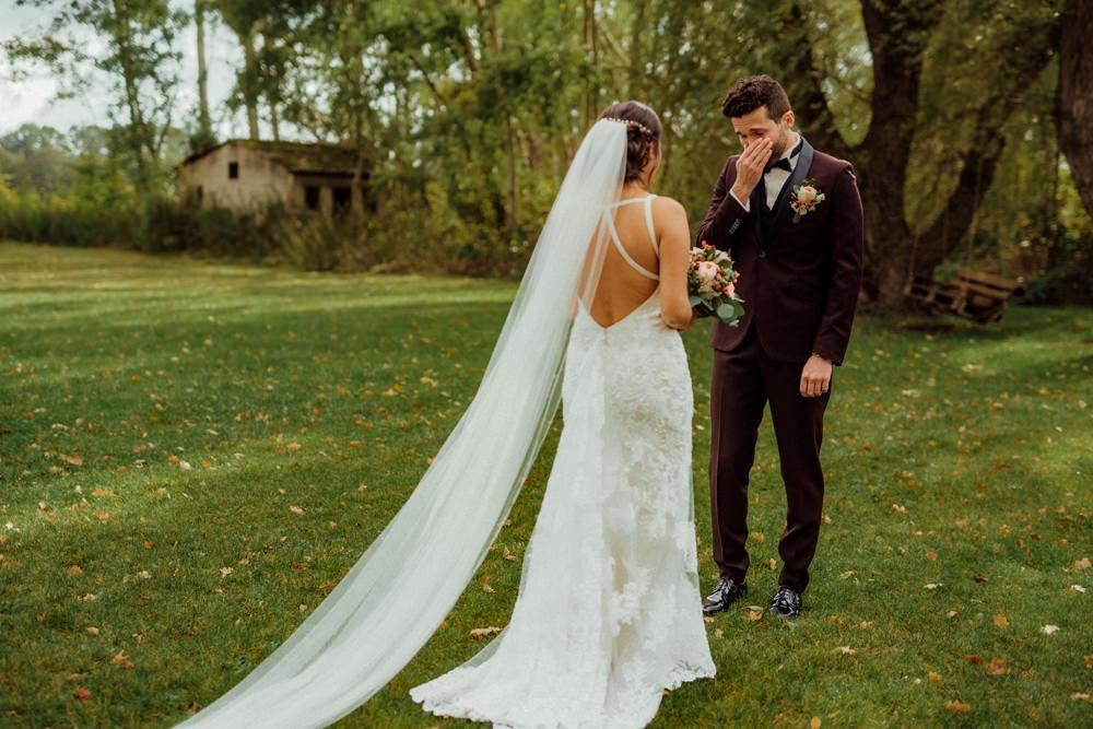 First Look. Bräutigam sieht Braut zum ersten Mal auf einer Wiese und ihm kommen die Tränen.