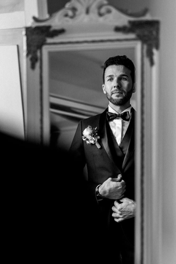 Getting Ready. Bräutigam sieht sich zum ersten Mal im Spiegel, nachdem er fertig gestylt für seine eigene Hochzeit ist.