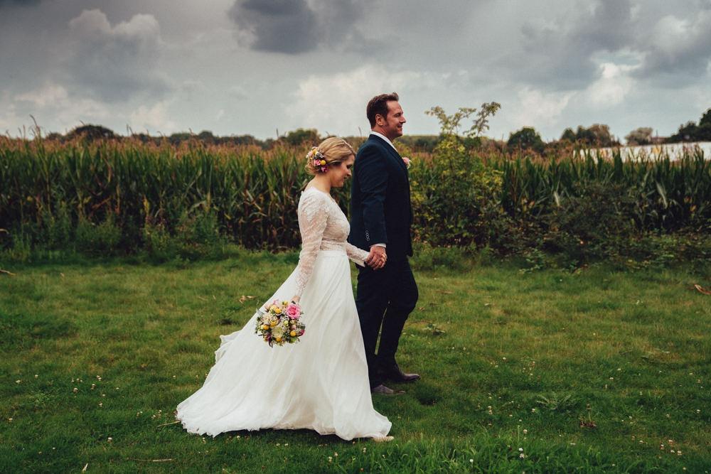 Kurz nach dem Gewitter geht ein Brautpaar im Wind an einem Maisfeld vorbei. Dunkle Wolken sind im Hintergrund zu sehen.