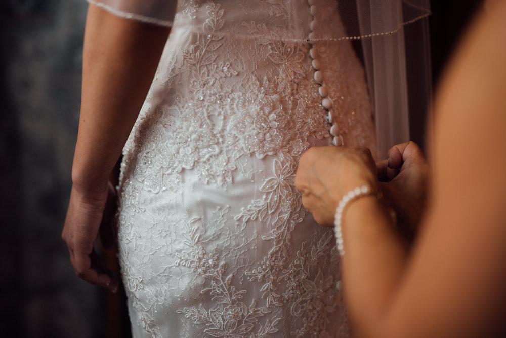 Brautmutter hilft der Braut beim Getting Ready ihr Kleid anzuziehen. Sie knöpft behutsam das Brautkleid zu.