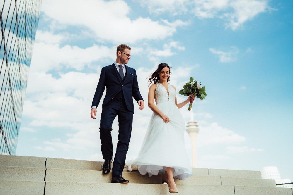 Brautpaar am Düsseldorfer Hafen mit Strahlend blauem Himmel. Beide schreiten eine Treppe herunter, Wind weht durch ihre Haare.