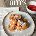 funnel cake bites on grey plate with strawberry sauce in grey bowl