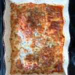 Baked ravioli in cream colored wavy dish