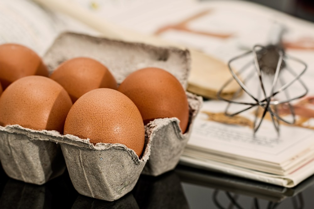 brown eggs in carton with whisk and recipe book