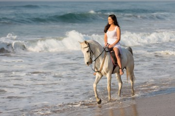 pretty young lady riding a horse on the beach in early morning