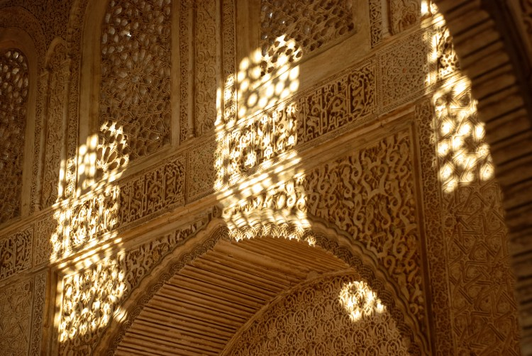 Intricate carvings within the Alhambra are further enhanced by the interplay of light.