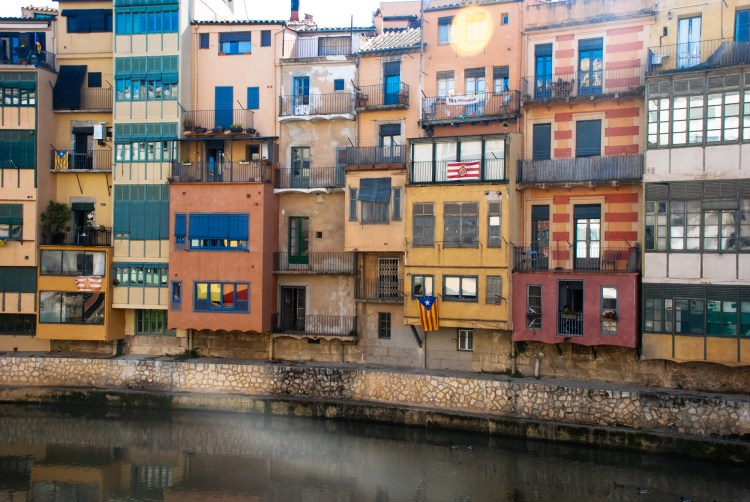 Pastel coloured buildings follow the curve of the Onyar River, Girona, Catalonia