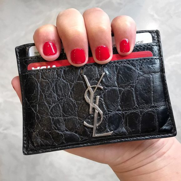 Hand with red nails holding a Black Embossed Crocodile Leather Saint Laurent YSL Monogrammed Card Case