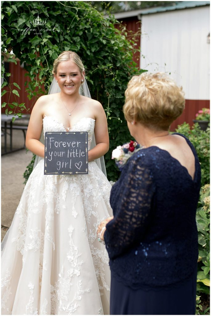 bride holding forever your little girl sign