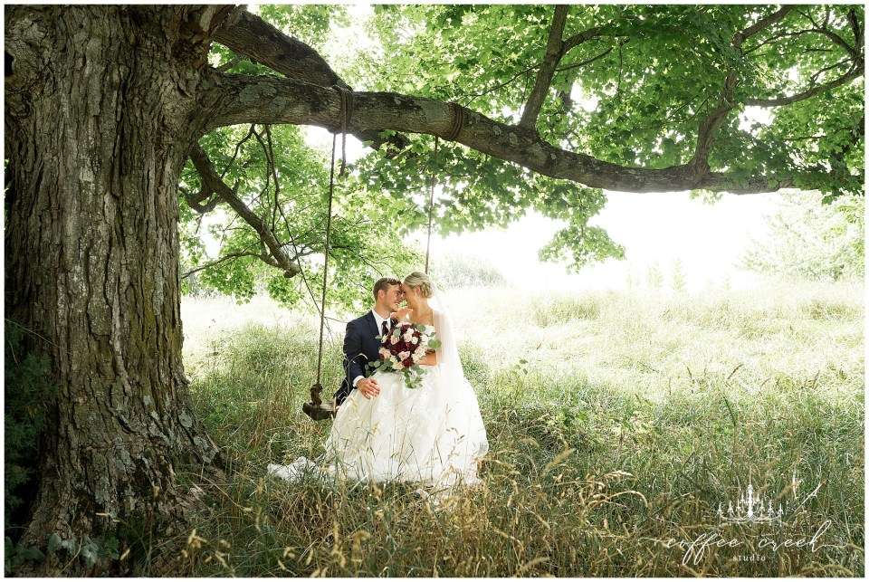 bride and groom on tree swing at barn venue wedding