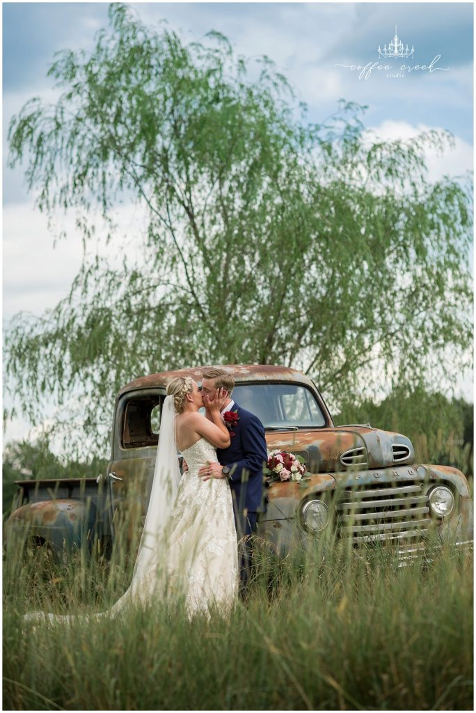 bride and groom on truck at barn venue wedding