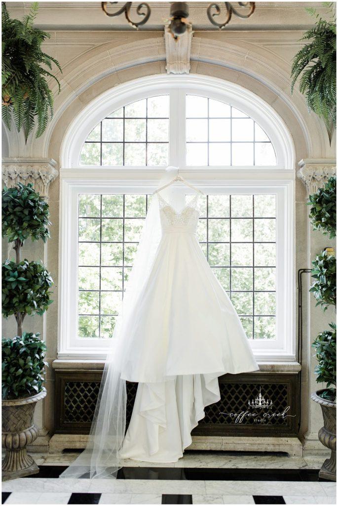 Wedding dress hanging in window at Laurel Hall Wedding