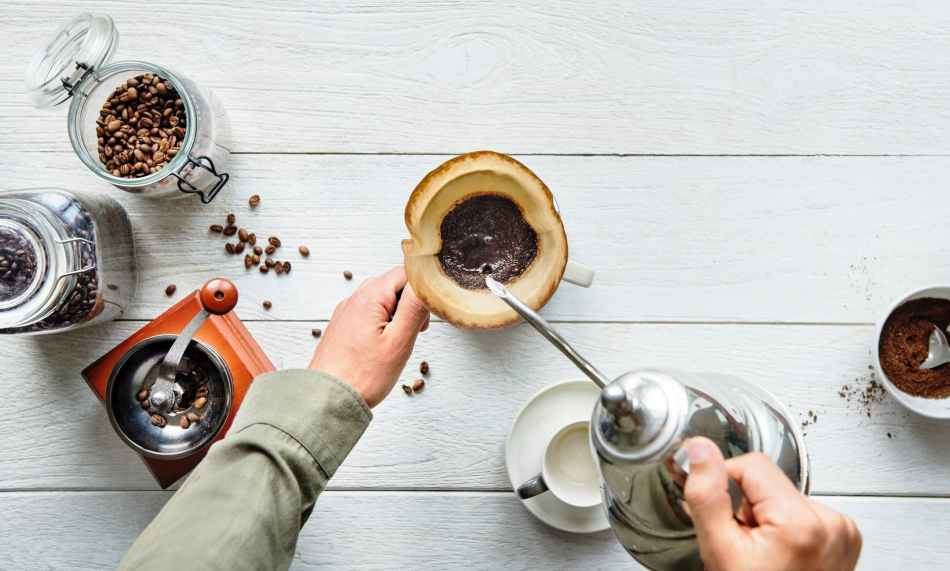 person pouring hot water in mug with ground coffee