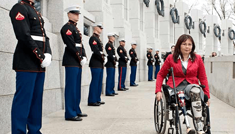 a lady in a wheelchair going by marines lined up