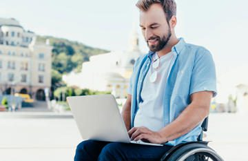 happy man in a wheelchair using a laptop