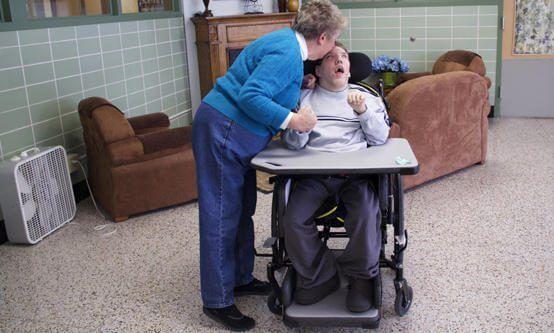 woman kisses forehead of a man in a wheelchair