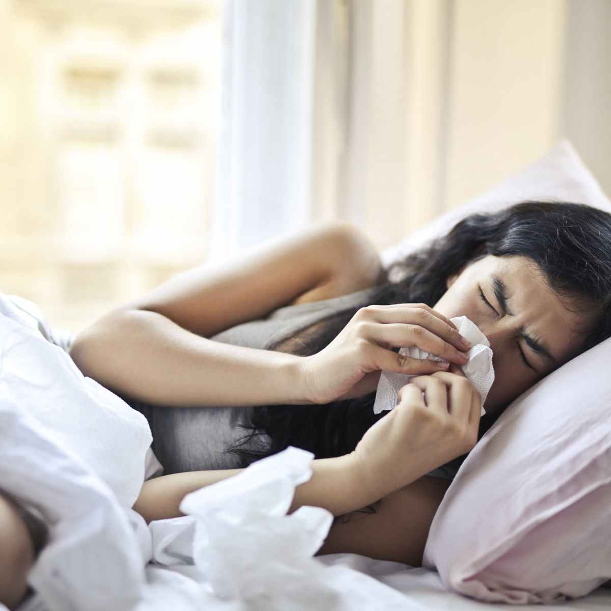 woman lying on bed while blowing her nose