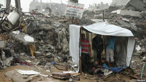 Palestinians take cover from rain inside a makeshift shelter near the ruins of their houses east of Gaza City, October 19, 2014.  Photo by Reuters
