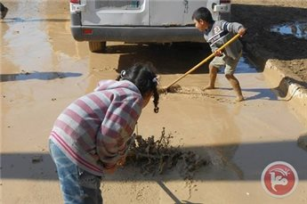 Children clear water after flooding in Gaza. Photo by MaanImages