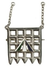 Holloway brooch designed by Sylvia Pankhurst. Comprising a porcullis symbol of the House of commons, the gate and hanging chaines in silver and the superimposed broad arrow in purple, white and green enamel. Referred to in Votes for Women, 16 April 1909 and first presented to ex-suffragette prisoners at a mass demonstration at the Albert Hall on 29th April 1909.