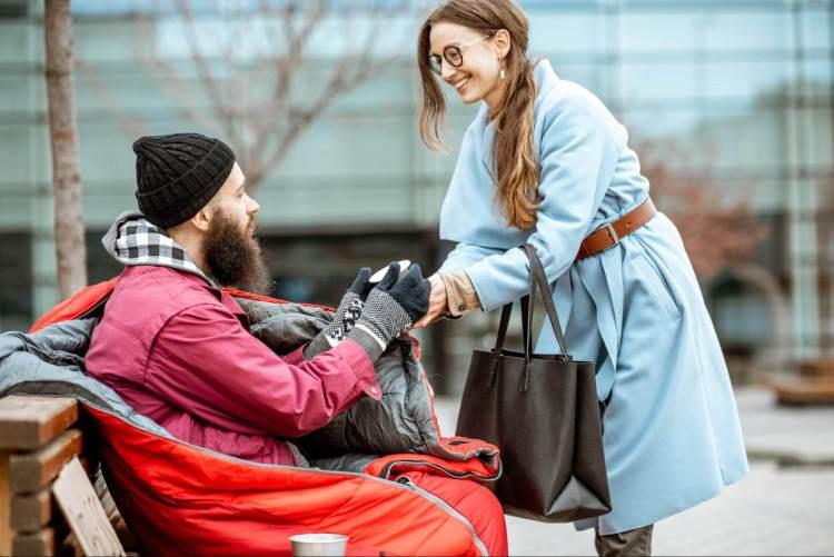 Eine Frau gibt einem armen Mann, der auf einer Bank sitzt, Geld