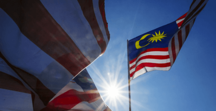 A Malaysian flag blowing in the wind with a bright sun shining from behind