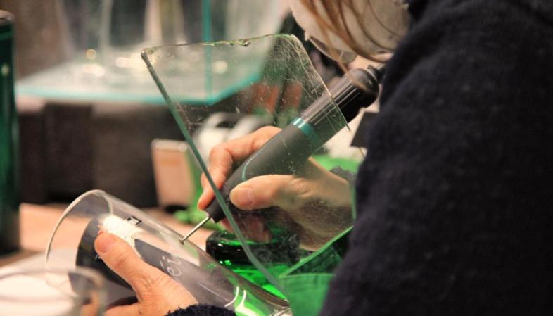 Funcionária do Heineken Experience gravando um copo adquirido na loja da atração.