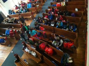 Recently-released asylum seekers fill the pews of the worship center. (Photo courtesy SAMC)
