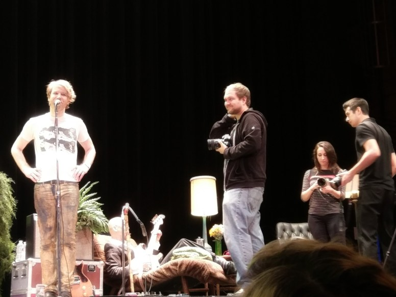 Videographer Kevin Barton smiles on stage. Kevin Barton never smiles. Also pictured: Kristen Forkheim and Matt Buikema.