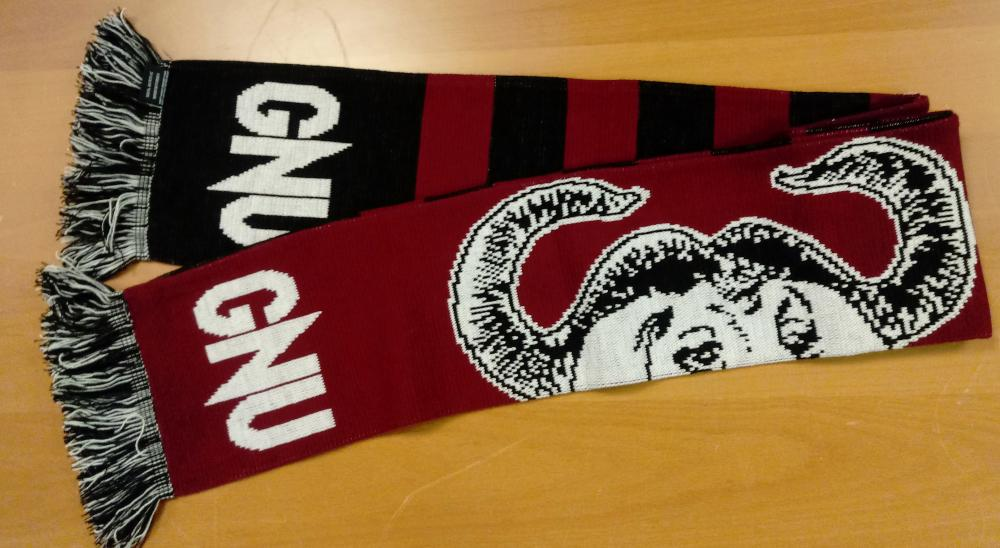 Bufanda en rojo oscuro con el logo ñu (Beanie), unas bandas más oscuras y las siglas GNU en los finales de la prenda.