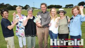 Apollo Bay residents, from left, Andrew Cosgriff, Linden Shields, Denise Byng, Felix the lamb, Tony Webber, Georgie Harrison, Liz Haughton and Gayle Seach support the return of the Apollo Bay Show next year after the event failed to go ahead this year.