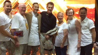 Cyrus Villanueva, third from left, celebrates his win on The X-Factor with, from left, brother Jonathan Villanueva, grandfather Alan Gray, mentor and music star Chris Isaak, grandmother Nola Gray, mother Tracie Villanueva and father Jo Villanueva.