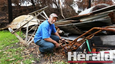 Separation Creek resident Peter Jacobs searches through the damage at his property after the Wye River-Jamieson Creek fire, which destroyed 116 homes on Christmas Day. Mr Jacobs is disappointed with the recovery process and the lack of help homeowners have received to rebuild and restore businesses.