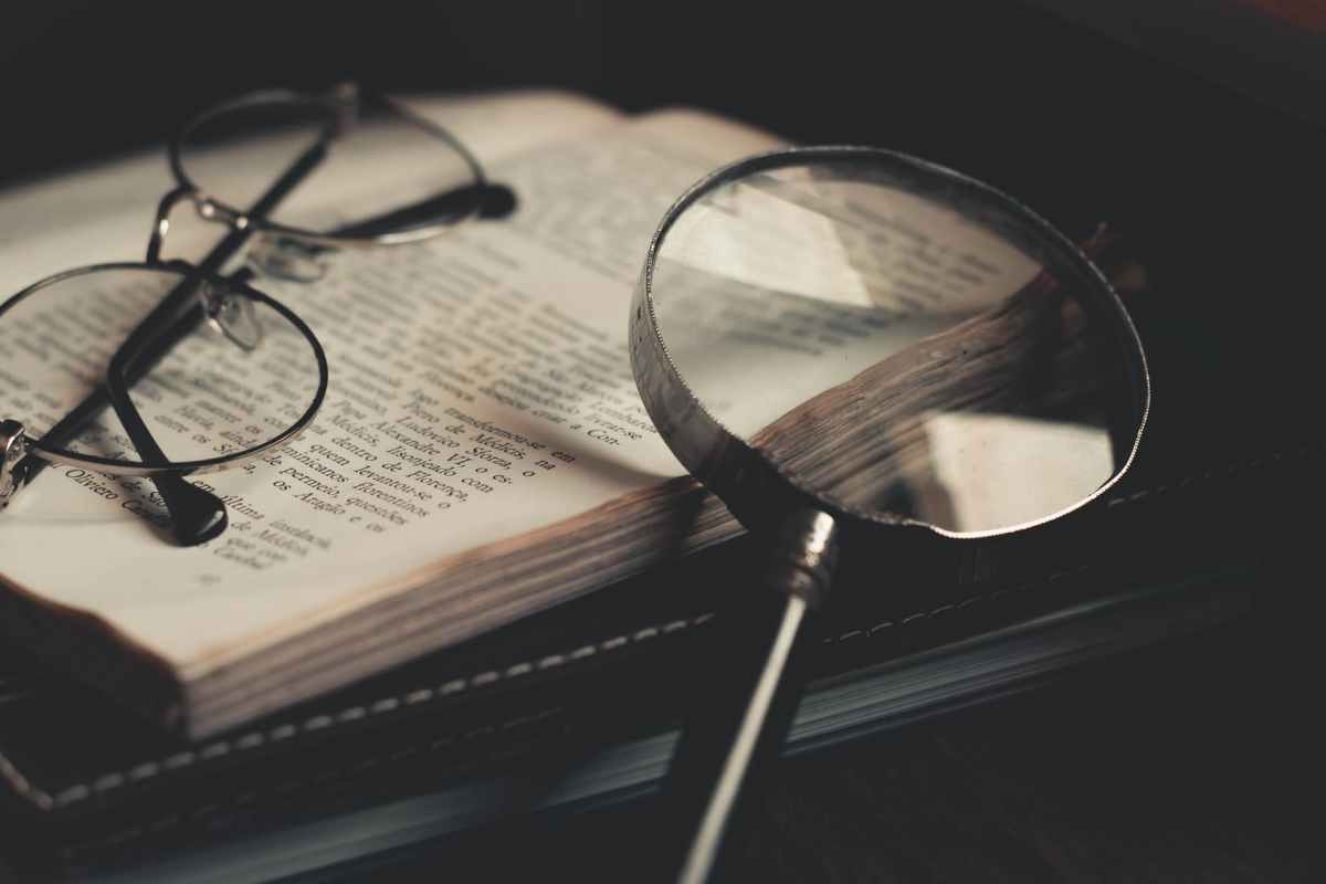 gray magnifying glass and eyeglasses on top of open book