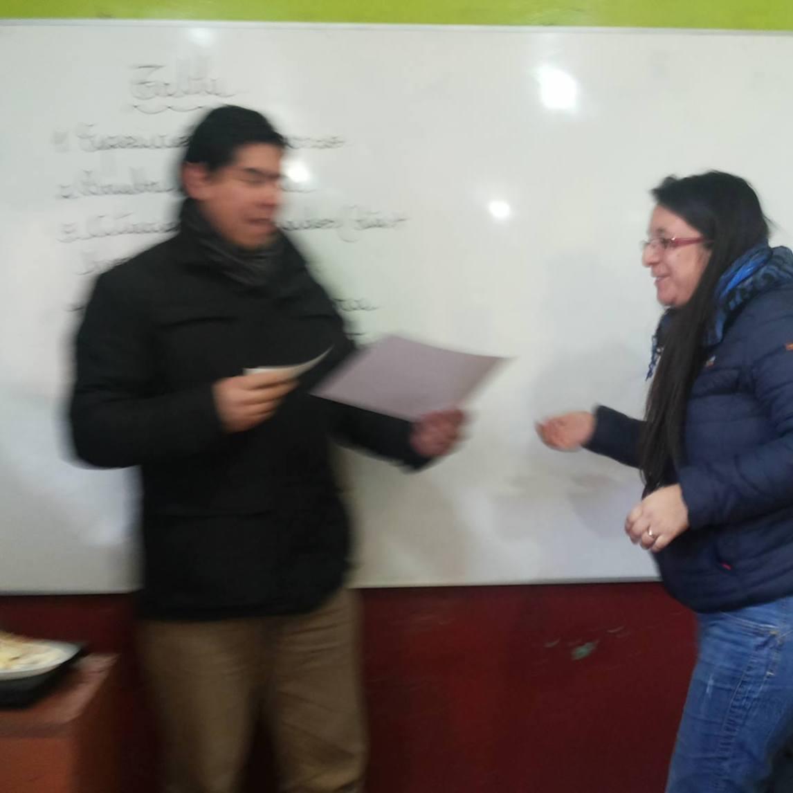 Elisabeth Gómez recibe diploma e incentivo de premiación de manos del sostenedor.
