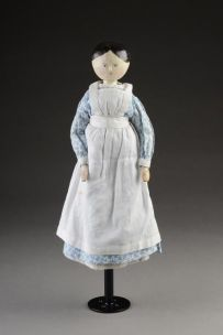 GRSRM : 1977.27.1 This wooden doll was a present to the Clerk's daughter, Molly Butcher, by inmates of Thursford Workhouse. It is a rare representation of a workhouse nurse.